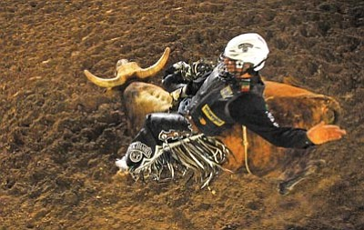 Matt Hinshaw/The Daily Courier<br /><br /><!-- 1upcrlf2 -->Rocky McDonald of Chihuahua Mexico holds on tight to Monkey Man during the Cowboy Capital Professional Bull Riding event at the Prescott Rodeo Grounds August 13, 2011.