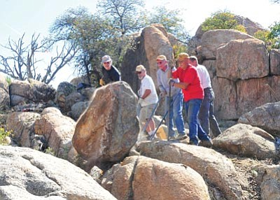 Les Stukenberg/The Daily Courier<br> Members of the Over the Hill Gang move a boulder as they work on the new Watson Lake Trail.