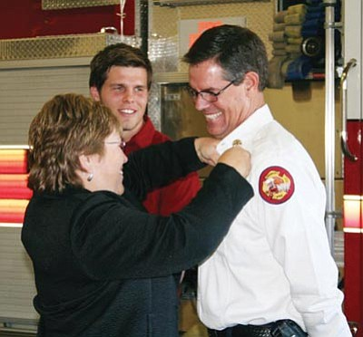 Courtesy photo/Prescott Fire Department<br>Prescott Fire Department Chief Bruce Martinez smiles as his wife Brenda pins on his fire chief badge in November 2009 while his son Mitch looks on.