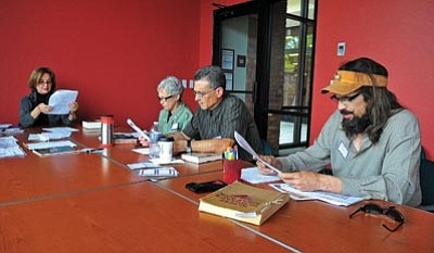 Matt Hinshaw/The Daily Courier<br> Tim Jennings, right, reads a poem while fellow poetry club members – from right, Neil Merino, Frances Thomas and Dr. Janet Preston – follow along Wednesday afternoon at the Prescott Public Library.