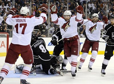 Phoenix Coyotes right wing Shane Doan, center, celebrates his goal with right wing Radim Vrbata, left, and center Martin Hanzal, as Los Angeles Kings defenseman Drew Doughty, second from left, and goalie Jonathan Quick sit in front of the goal during Sunday's game in Los Angeles. <br> Mark J. Terrill/ The Associated Press