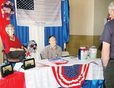 Cheryl Hartz/Courtesy photo<br> Prescott Valley Town Council member Lora Lee Nye and Deputy Town Manager Ryan Judy man a booth for Prescott Valley Healing Field of Northern Arizona at the annual Home and Garden Show Saturday at Tim's Toyota Center in Prescott Valley.