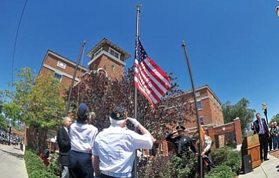 Matt Hinshaw/The Daily Courier<br> Lt. Colonel John Mortimer, U.S. Army (Ret.), salutes the American flag as it is raised over the Hassaympa Inn for the first time in  50 years Saturday morning in downtown Prescott.