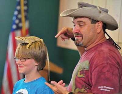 Matt Hinshaw/The Daily Courier<br> Wildlife expert Wildman Phil of Casa Grande, Ariz., places a bearded dragon on 10-year-old Corey Kolasinski's head during his live creatures presentation at the Prescott Public Library Thursday afternoon in Prescott.