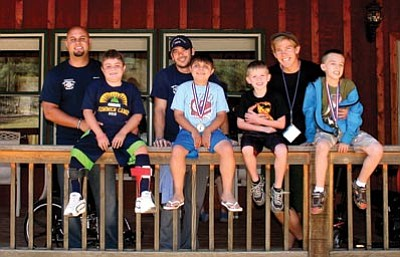 Williamson Valley Fire District/Courtesy photo<br> Williamson Valley Firefighters Jason Reedy, Brandon Rollins and Sean Kauffman with pose with kids at the annual Muscular Dystrophy Association camp in Payson earlier this month.