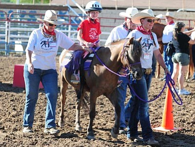 """Les Stukenberg/The Daily Courier<br>Annabelle Jamison, 7, of Chino Valley takes a horseback ride during the annual Happy Hearts Rodeo for Exceptional Children before the opening performance of the Prescott Frontier Days """"World's Oldest Rodeo"""" Thursday night."""