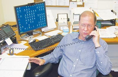 Ken Hedler/The Daily Courier<br>Rick Marcum, director of the Small Business Development Center in Prescott, talks on the phone Wednesday to a client who is expanding her business into international trade.