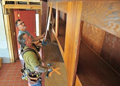 Matt Hinshaw/The Daily Courier<br>Tim Pawol, foreground, a carpenter with Board by Board Builders, and Robert Board, owner of Board by Board, remove some cabinets in a home they are fully remodeling Wednesday morning in Prescott. The home was originally built in 1965 and will be remodeled into a modern open space design.