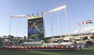 In this photo taken July 10, 2012 photo, country singer Luke Bryan is projected on the scoreboard as the sings the national anthem before the MLB All-Star baseball game in Kansas City, Mo. (AP Photo/Charlie Riedel)