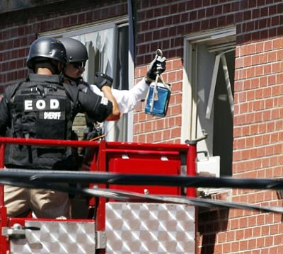 "Alex Brandon/The Associated Press<br> Members of law enforcement wearing body armor and helmets prepare to what ATF sources describe as a""water shot"" in the apartment of alleged gunman James Holmes Saturday in Aurora, Colo. The ""water shot"" is exploded and used to disrupt dangerous devices."