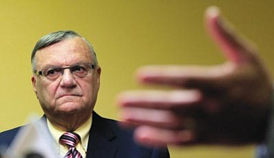 Ross D. Franklin/The Associated Press<br> Maricopa County Sheriff Joe Arpaio listens to one of his attorneys during a news conference in Phoenix April 3. Arpaio  faces allegations that his trademark immigration sweeps amounted to racial profiling against Hispanics.