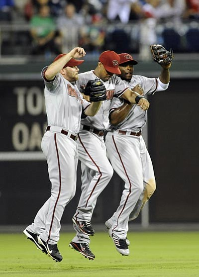 Arizona Diamondbacks Jason Kubel, left, Chris Young, middle, and Justin Upton celebrate at the end of a baseball game against the Philadelphia Phillies, Friday, Aug. 3, 2012, in Philadelphia. The Diamondbacks won, 4-2. (AP Photo/Michael Perez)