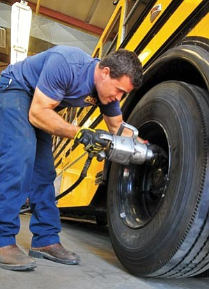 Matt Hinshaw/The Daily Courier<br> Rex Pehl, a Prescott Unified School District vehicle mechanic, changes a tire on a school bus Wednesday afternoon at the PUSD transportaion yard in Prescott.  The first day of school for PUSD will be Monday, Aug. 6.