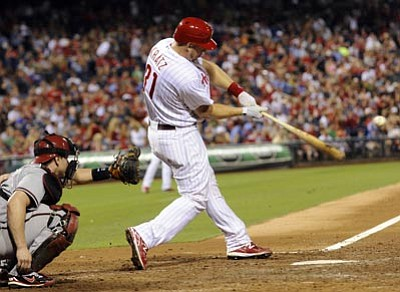 Philadelphia Phillies' Erik Kratz hits a ball in front of Arizona Diamondbacks' Miguel Montero in the seventh inning of a baseball game, Saturday, Aug. 4, 2012 in Philadelphia. Kratz homered and drove in a pair, leading the Phillies to a 3-0 victory over the Diamondbacks . (AP Photo/Michael Perez)