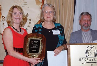 Joanna Dodder/Daily Courier<br> Heidi Osselaer, left, gets the Sharlot Hall Award Saturday from last year's winner Nancy Burgess and Sharlot Hall Museum Director John Langellier.