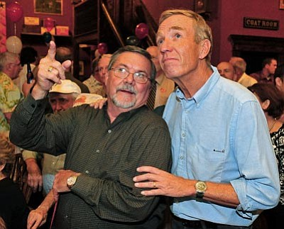 Matt Hinshaw/The Daily Courier<br> Supervisor District 2 incumbent Tom Thurman and Supervisor District 1 candidate Rowle Simmons watch as results from their races being to roll in on the Yavapai County website Tuesday night at the Palace Restaurant and Saloon in downtown Prescott.