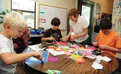 Les Stukenberg/The Daily Courier<br> Pamela Brown helps fourth- and fifth-grade students at the Primavera School work on their poetry art journals. Brown has taught at the school for 38 of the 40 years the school has been in existence.