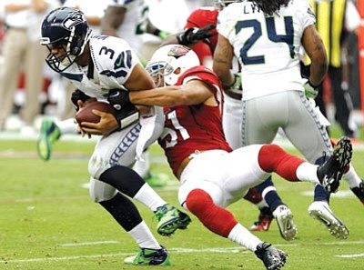 Ross D. Franklin/The Associated Press<br> Seattle Seahawks' Russell Wilson (3) is sacked by the Cardinals' Paris Lenon during the first half of Sunday's NFL game in Glendale. The Cardinals beat the Seahawks 20-16.