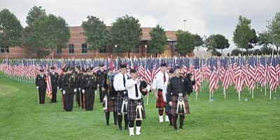 Photo courtesy Heidi Dahms Foster<br> Members of the Central Yavapai Fire District Honor Guard, the Prescott Valley Police Honor Guard, and bagpipers from the Prescott and Surprise areas stand next to the 9-11 Healing Field of flags, ready to post the colors during the ceremony.