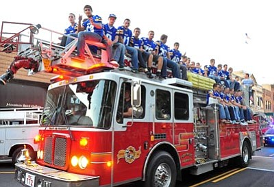Matt Hinshaw/The Daily Courier<br>The Prescott High School Varsity football team waves to the crowd while riding on top of the Prescott Fire Deparment's Ladder 72 fire truck Thursday evening during the annual Homecoming Parade on Whiskey Row.
