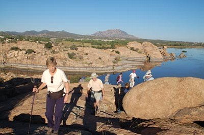 Cindy Barks/The Daily Courier<br> At right, Linda Schmitt tops the hill on a recent hike led by the TrekAbout Walking Club. This week's hike featured the new Willow Lake Loop Trail, which offers lake views and steep climbs over the rock formations of the Granite Dells.