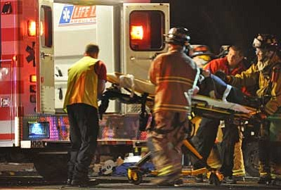 Heidi Dahms Foster/Special to The Courier<br> Emergency personnel load a patient they had extricated from her vehicle into an ambulance after a major collision Sunday night on Highway 69 near