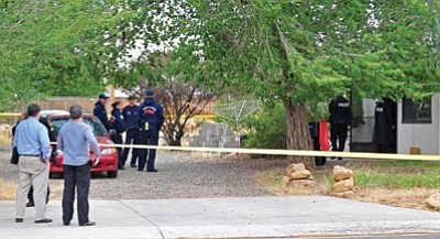 Matt Hinshaw/The Daily Courier<br> Prescott Valley police officers survey the scene of a double homicide inside a home near the intersection of Robert Road and Lakeshore Drive in Prescott Valley Thursday afternoon.
