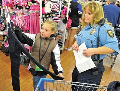 Matt Hinshaw/The Daily Courier<br>Radian Hart, 8, shows a pair of sparkle jeans to Prescott Animal Control Officer Shannon Gray Dec. 10, 2011, during the annual Shop with a Cop event at the Wal-Mart on Gail Gardner Way in Prescott.