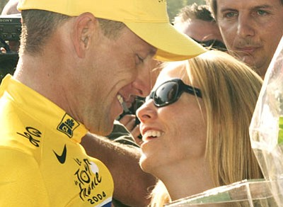 Franck Prevel/The Associated Press<br>In better days, back on July 25, 2004, Lance Armstrong kisses Sheryl Crow as he celebrates his sixth straight Tour de France win in Paris.