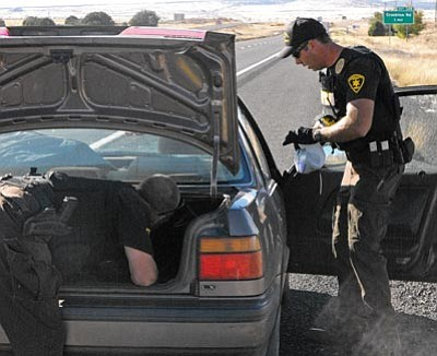 Scott Orr/The Daily Courier<br> Deputy Harry Shrum digs through the trunk as Deputy Randy Evers searches the front seat of a car for drugs after a stop on I-40 west of Ash Fork.