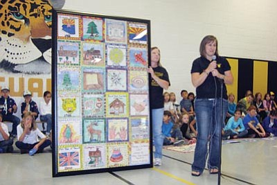 Abia Judd Elementary School/Courtesy photo<br> Abia Judd Elementary School PTA President Jennifer Carter unveils the framed centennial quilt that Abia Judd students made Nov. 2 during an assembly at the school.