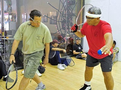 Matt Hinshaw/The Daily Courier<br>  Volunteer Ben Sialega, right, works with U.S. Army Veteran Dennis Wirght on the racquetball court Saturday afternoon at the Prescott Downtown Athletic Club.