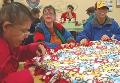 Lisa Irish/The Daily Courier<br> Rayma, left, and Rena, center, who asked that their last names not be used, and Keith Mason, right, with the Special Needs Activity Program, make baby blankets for the Crisis Pregnancy Center during their craft night Thursday, Nov. 15 at the Adult Center in Prescott.