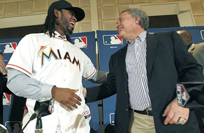 LM Otero/The Associated Press<br>In this Dec. 7, 2011, file photo, Marlins owner Jeffrey Loria, right, and then-newly signed free-agent shortstop Jose Reyes are all smiles during MLB's Winter Meetings.