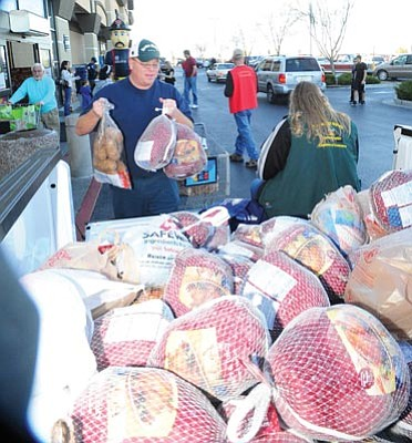 Les Stukenberg/The Daily Courier<br>Russ Lorton of Prescott Valley donates two turkeys and a sack of potatoes to the Flying High Turkey Drive at the Prescott Valley Fry's store Monday afternoon.