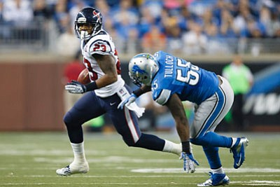 Rick Osentoski/The Associated Press<br>Texans running back Arian Foster (23) runs past Lions middle linebacker Stephen Tulloch during overtime Thursday in Detroit.