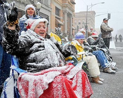 Matt Hinshaw/The Daily Courier<br>Carol David and other paradegoers wave and cheer last year during the 29th annual City of Prescott Christmas Parade. The 30th annual parade starts Saturday at 1 p.m. in downtown Prescott.