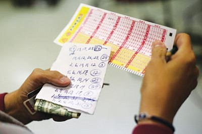 Patrick Semansky/The Associated Press<br> Sharon Long double-checks her Powerball numbers as she stands in line at a convenience store in Baltimore Wednesday.