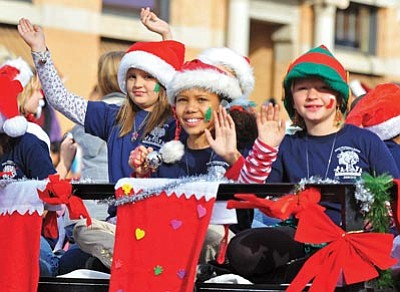 Matt Hinshaw/The Daily Courier<br>Children with Acorn Montessori Charter School out of Prescott Valley wave to the crowd as their float makes its way down Cortez Street Saturday afternoon during the 30th annual City of Prescott Christmas Parade.