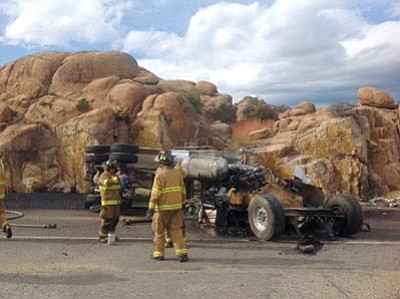 Don Rea/Courtesy photos<br> Fire and rescue crews survey the damage on Highway 89 after a dump truck rolled over, striking a passenger car Thursday.