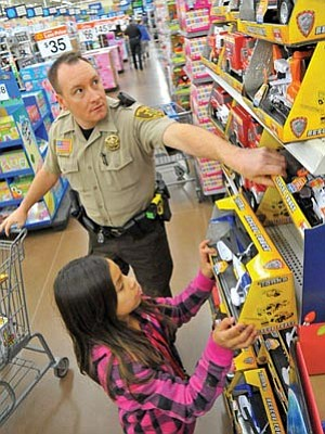 Matt Hinshaw/The Daily Courier<br>Yavapai County Sheriff's Office Deputy Lopez helps Ryleah Rodriguez, 9, pick out a toy helicopter for one of her relatives last year during the annual Shop with a Cop event at the Wal-Mart on Gail Gardner Way in Prescott.