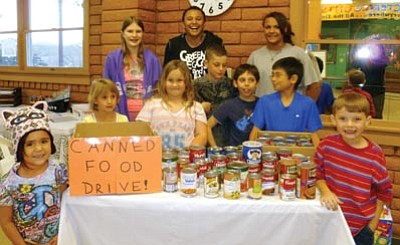 Courtesy the Boys & Girls Clubs of Central Arizona<br>Members of the Kids to Community program with the Boys & Girls Clubs of Central Arizona donated 100 cans of food to local shelters and food banks during their recent food drive.