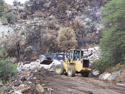 Courtesy Yavapai County<br> Yavapai County road crews try to clear boulders off County Road 59 on July 14, 2012, after a monsoon downpour caused flash flooding where the Gladiator wildfire had burned near Crown King.