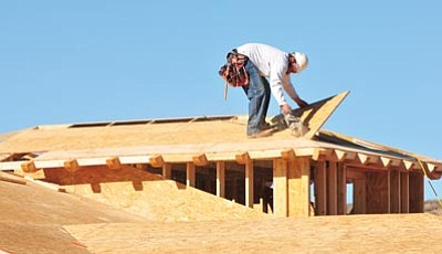 Les Stukenberg/The Daily Courier<br>A construction worker puts the finishing touches on roughing out a roof at a new home construction in the Stoneridge subdivision.