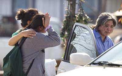 AP photo<br> Ana Leal, left, embraces Lone Star College student Sabrina Cuellar after she was evacuated and picked up by her mother, Maria Cuellar, right, from the campus following a shooting at the north Harris County school, Tuesday in Houston. Authorities say the shooting was the result of an altercation between two people, and at least one was a student.