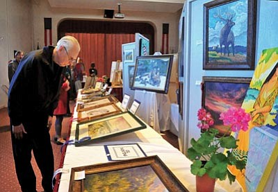 Matt Hinshaw/The Daily Courier<br>Howard Fromm checks out the painting section of the 20th Veterans Art Show Wednesday morning at the Bob Stump VA Medical Center in Prescott.