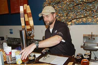 Ken Hedler/The Daily Courier<br> Damon Swafford, co-owner of Granite Mountain Brewing in downtown Prescott, prepares a sample tray of beers Sunday afternoon.