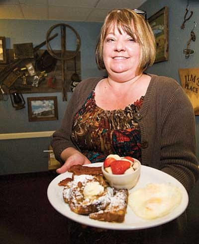 Les Stukenberg/The Daily Courier<br> Owner Dana Grimley holds a plate of French toast, eggs and bacon.