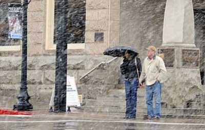 Les Stukenberg/The Daily Courier, file<br> Jane and Tim Griffin of Santa Cruz, Calif., wait at the stoplight at the corner of Gurley and Cortez streets as the snow flies in downtown Prescott on Dec. 7, 2009. The scene will likely be similar today, according to the National Weather Service.