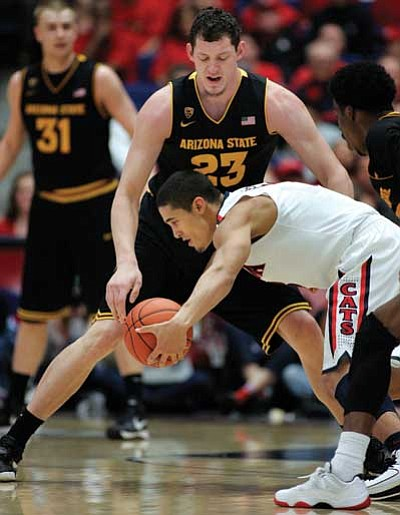 John Miller/The Associated Press<br> Arizona's Nick Johnson works to control the ball during UofA's matchup Saturday against ASU in Tucson. Johnson led the Wildcats with 17.